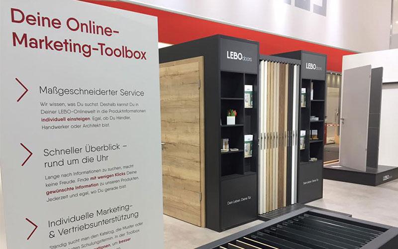 POS-Modul mit ausziehbaren LEBO-Türen. Im Vordergrund Wand mit Beschreibung der Marketing-Toolbox.