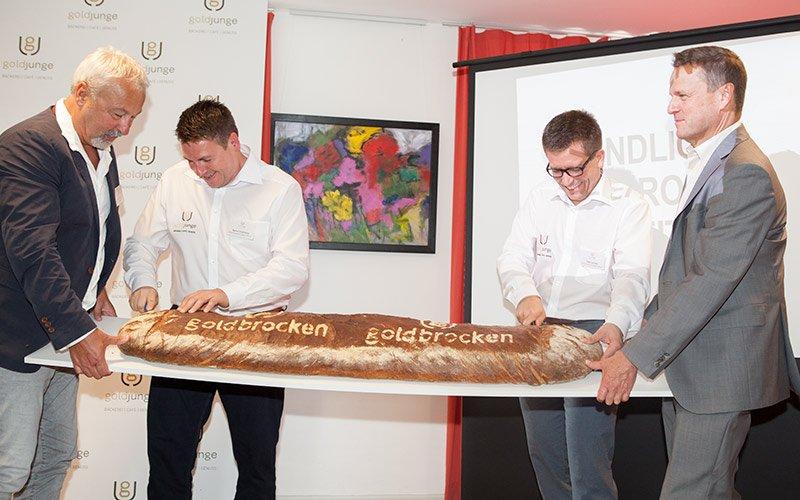 Das Brot wird bei der Eröffnung des goldjungen nach Markenentwicklung angeschnitten